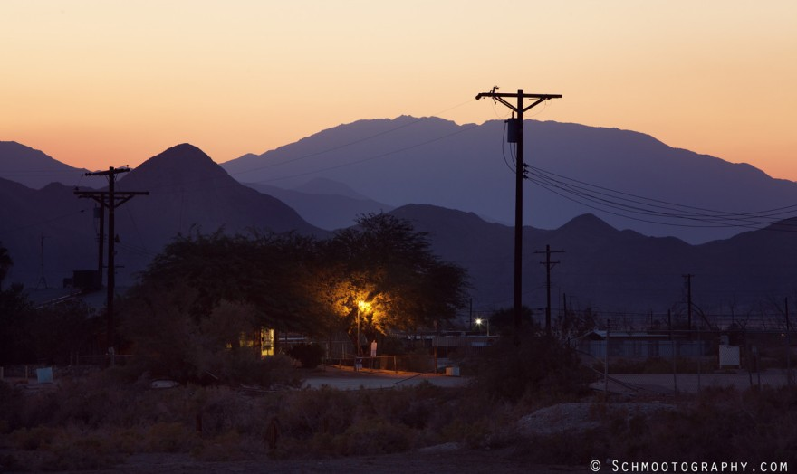 The mountains are little but a goal in the distance. Street lamps start to flicker in the desert dusk, but there's little to illuminate as there is little traffic of any kind, here.